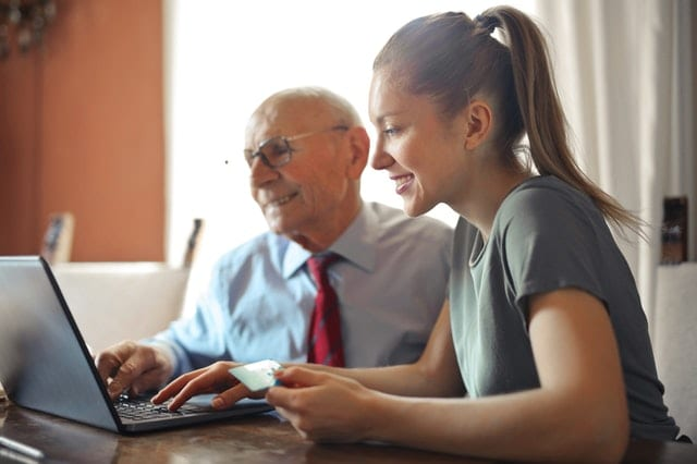 A woman helping a senior man make a payment on the internet.
